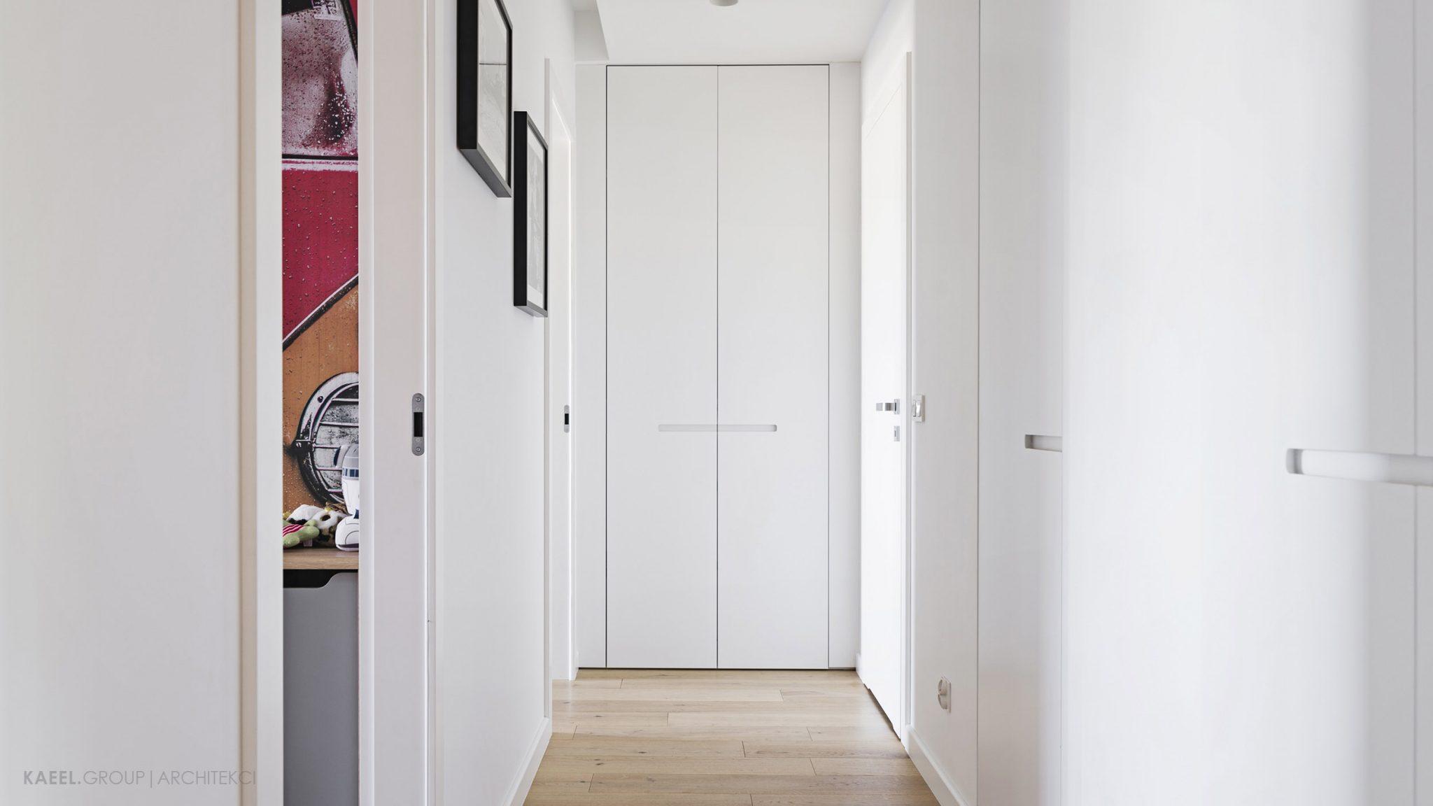 Minimalistyczny korytarz z wnękową szafą